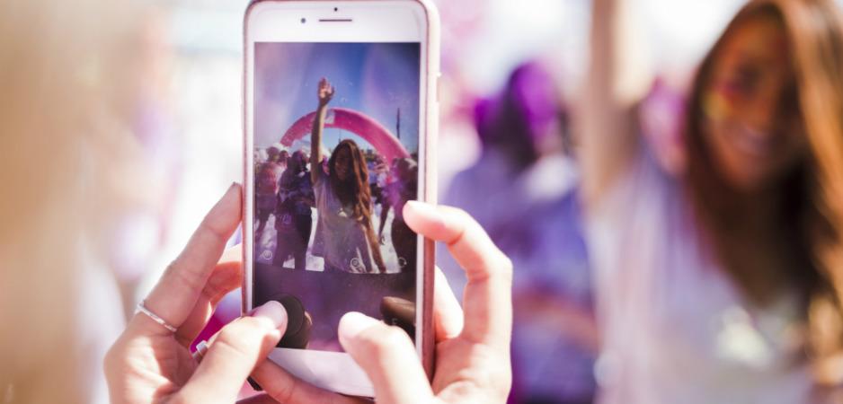 Bilde av noen som fotograferer en dansende jente med telefonen sin
