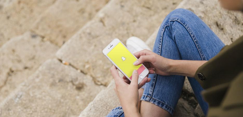 Bilde av en som ser på snapchat på telefonen