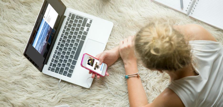Bilde av kvinne som ser på telefonen sin og pc-skjermen